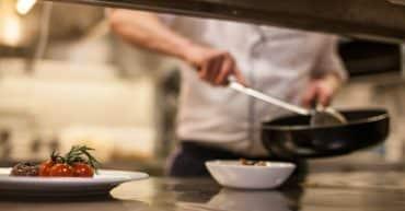 Chef cuisinier préparant un plat sur un chauffe plat