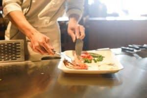 Chef cuisiner préparant un plat sur un plan de travail